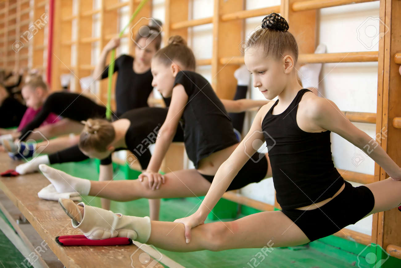 preteen stretch gymnast: Young girl gymnasts in training - stretching Stock Photo