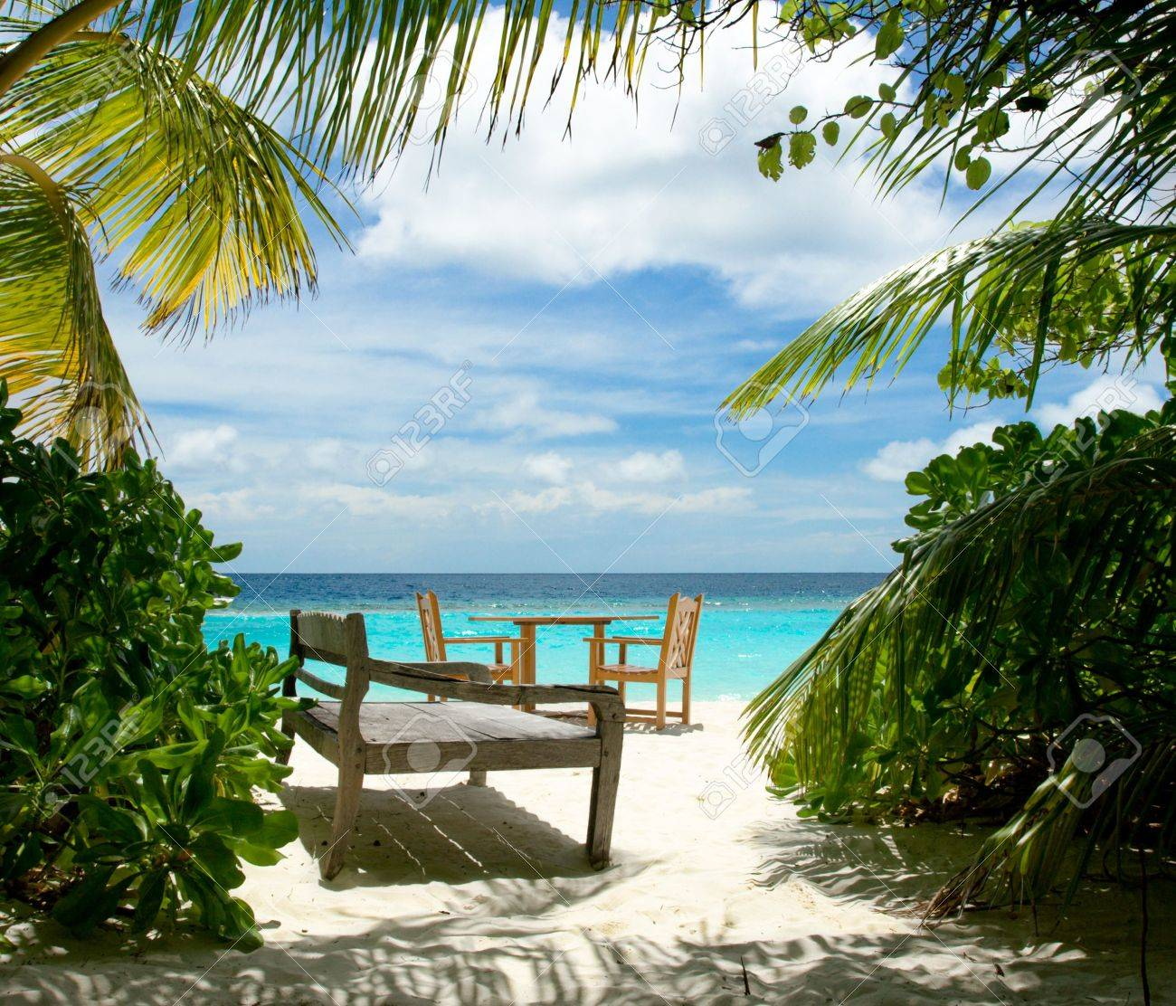 Free table for two and wooden sun bed on the tropical beach Stock Photo - 4672201