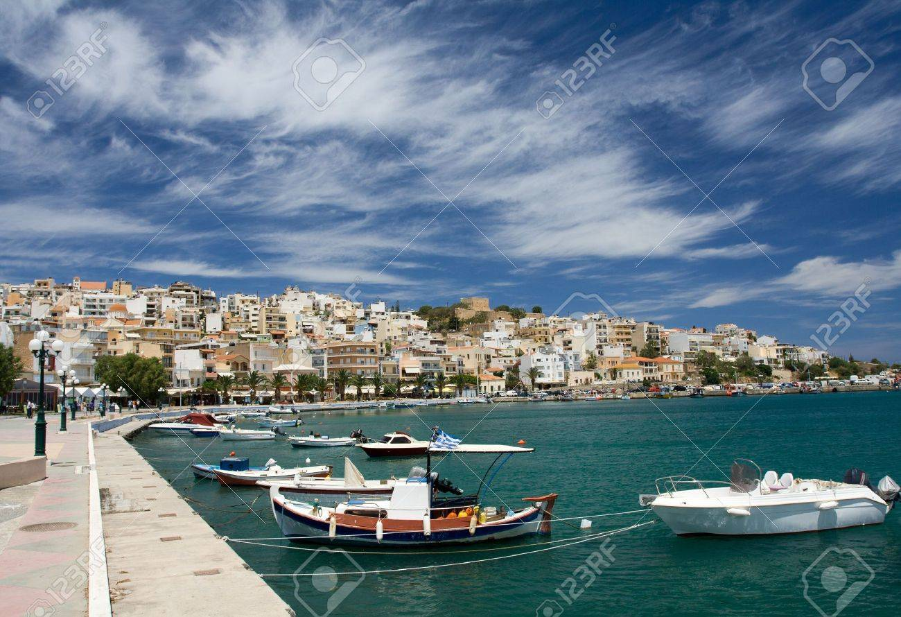 Sea bay with moored boats, promenade in Mediterranean town Sitia Greece Crete and dramatic cirrus clouds in the blue sky Stock Photo - 7179951