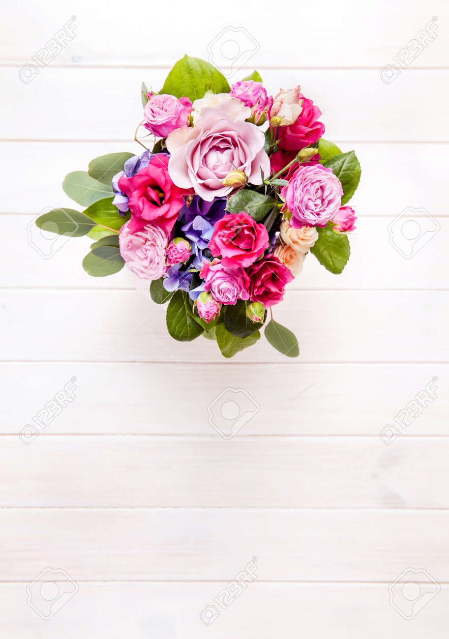 Flowers bouquet of roses in a bucket on a white wooden background flowers bouquet of roses in a bucket on a white wooden background stock photo izmirmasajfo
