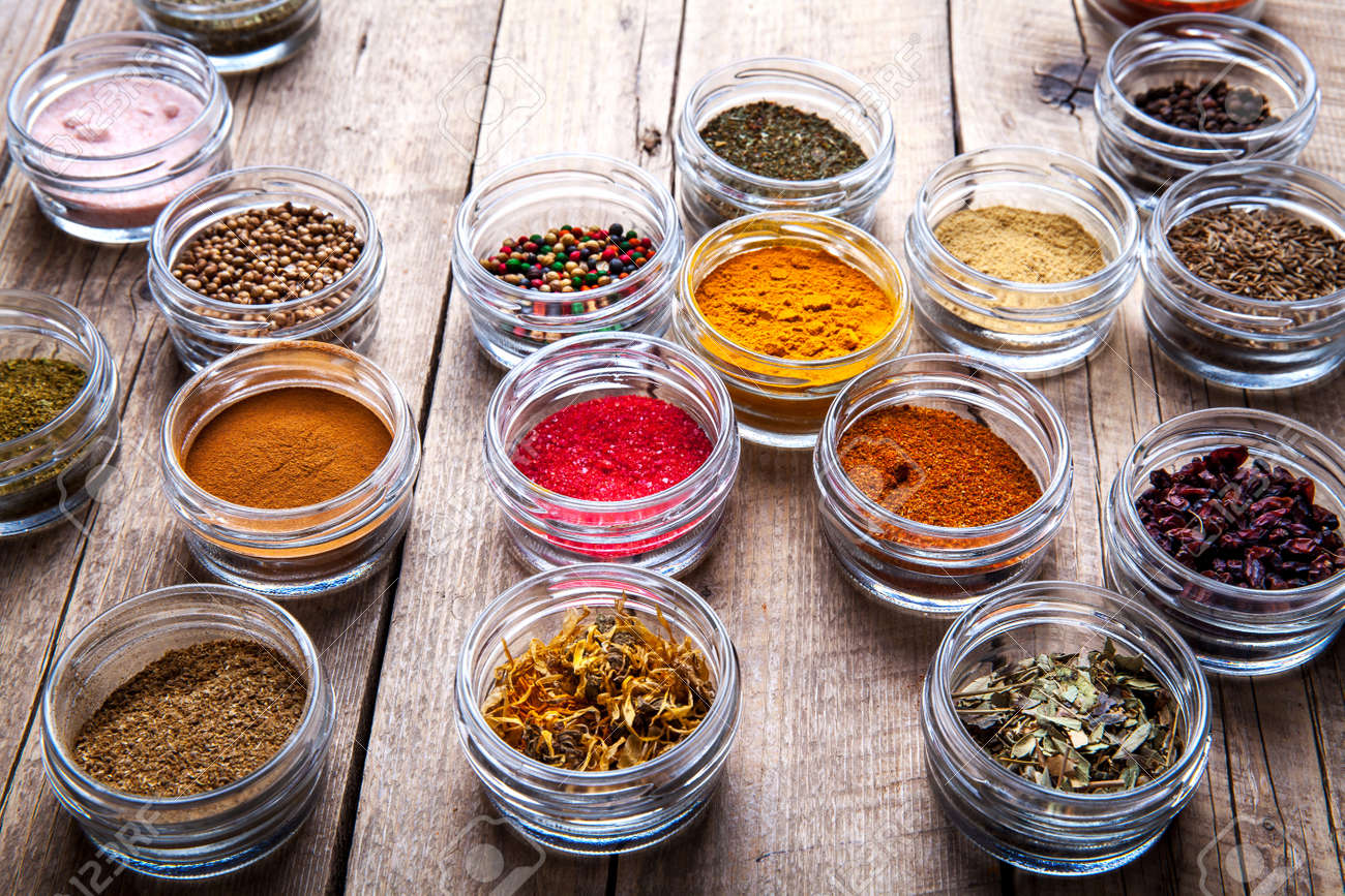 Spices in jars on wooden background. - 54580492