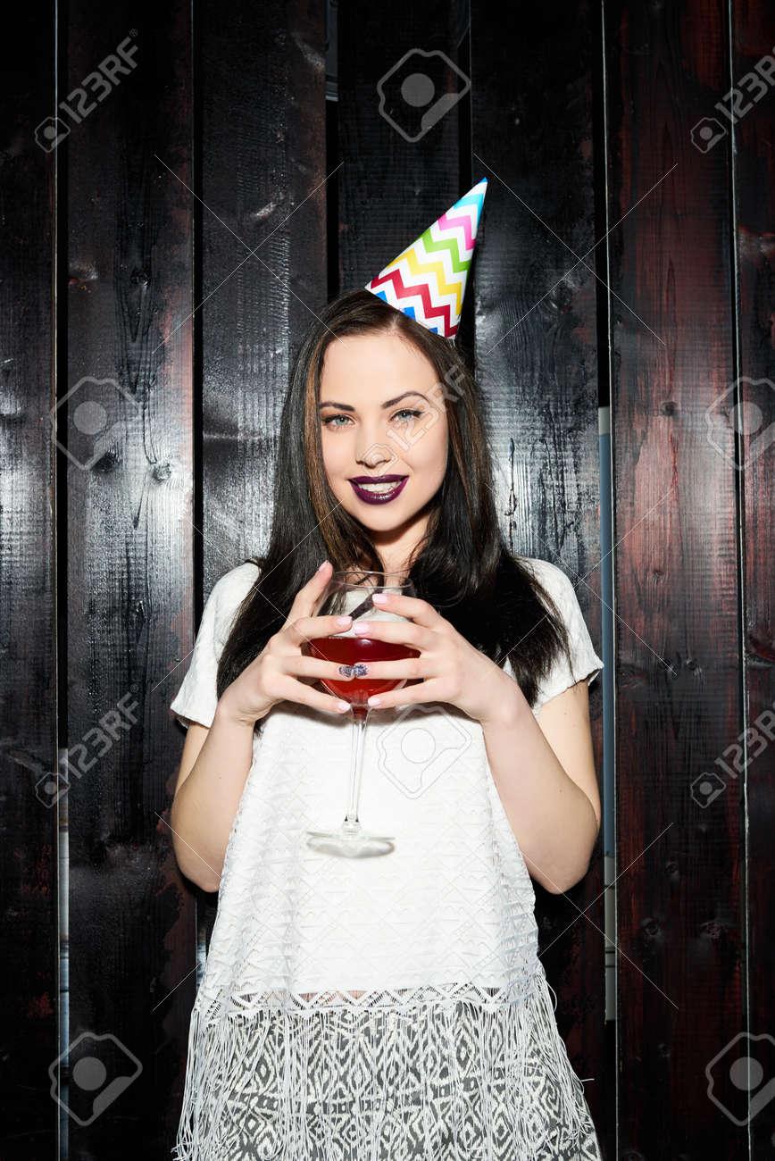 9cb8ab4c2a Foto de archivo - La mujer disfruta de la fiesta en un fondo negro de la  madera. Cumpleaños. Año nuevo.