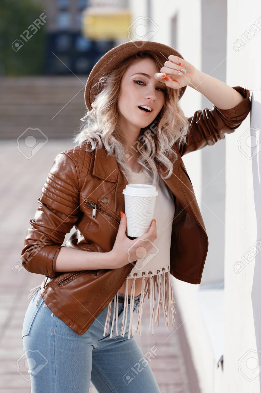Beautiful young girl is holding a paper cup of coffee model stock beautiful young girl is holding a paper cup of coffee model poses in front of voltagebd Images