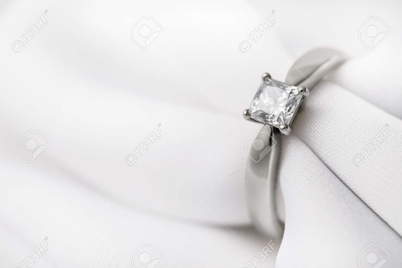 White gold wedding ring with a large diamond on a silk fabric with copy space, close-up - 123564077