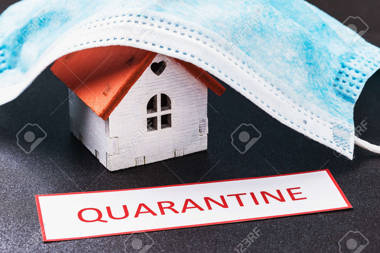 The toy house is covered with a medical mask and a tag with the inscription. Home quarantine concept - 142228227