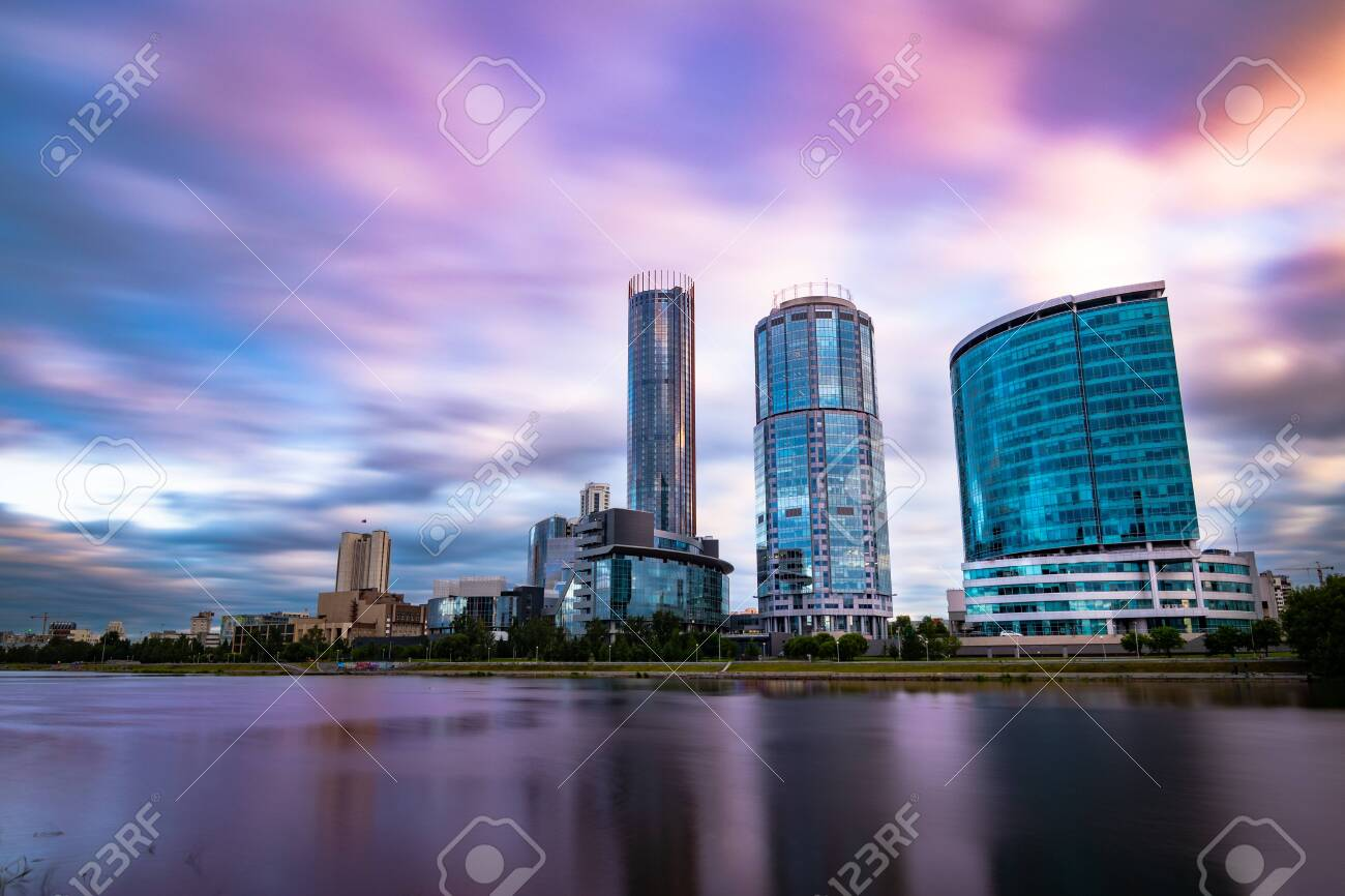 Beautiful wide angle long exposure cityscape of Yekaterinburg city, Russia at sunset with blurred blue and purple clouds. Skyscrapers reflecting in water of Iset river - 132070675