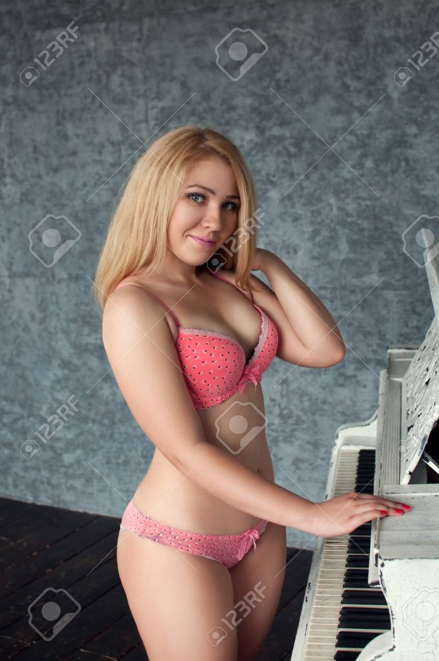 4a7468c1b7f plus size blonde female in pink underwear smiling and put her hand on the piano  Stock