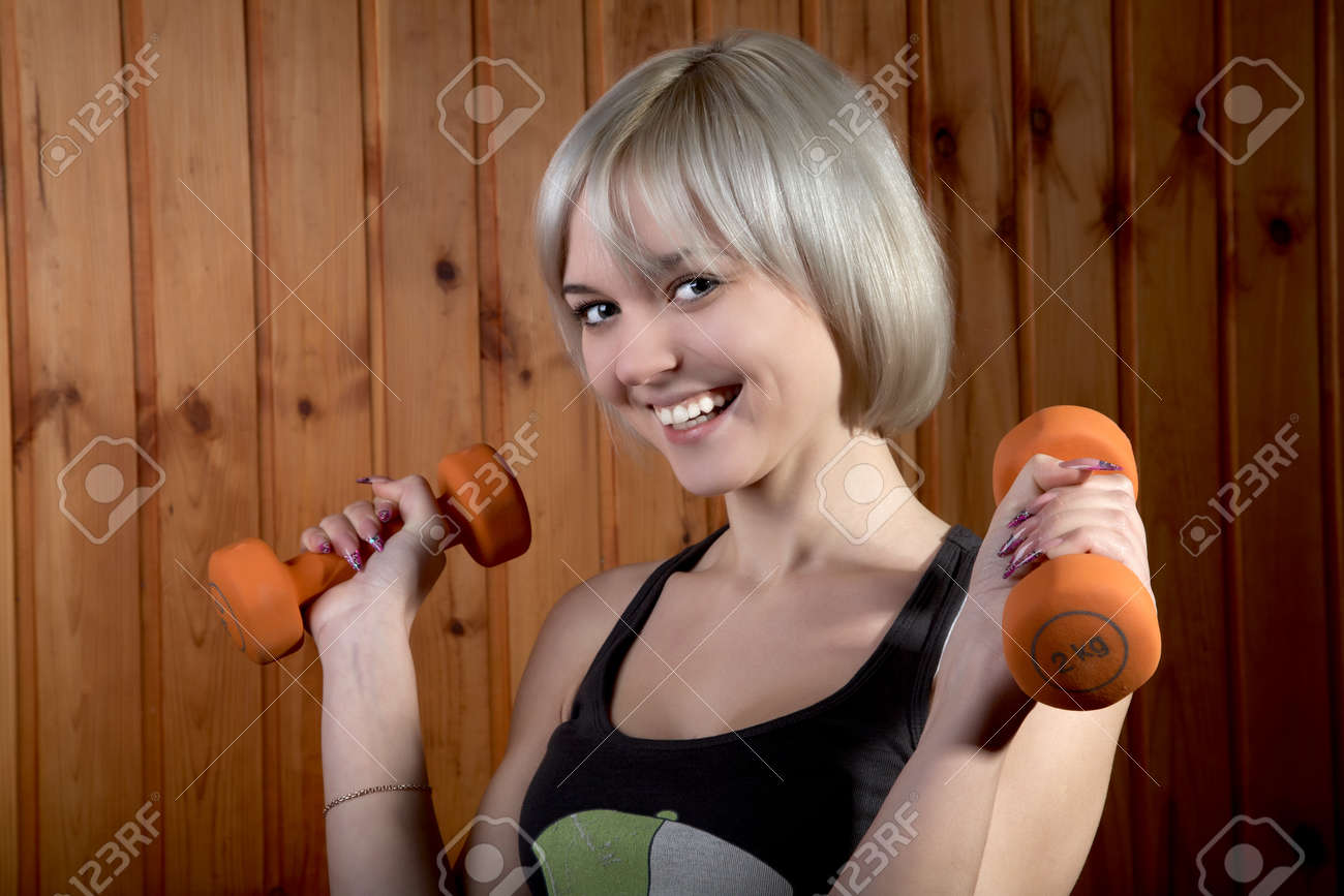 The cheerful girl with dumbbells against a wooden wall Stock Photo - 8855022