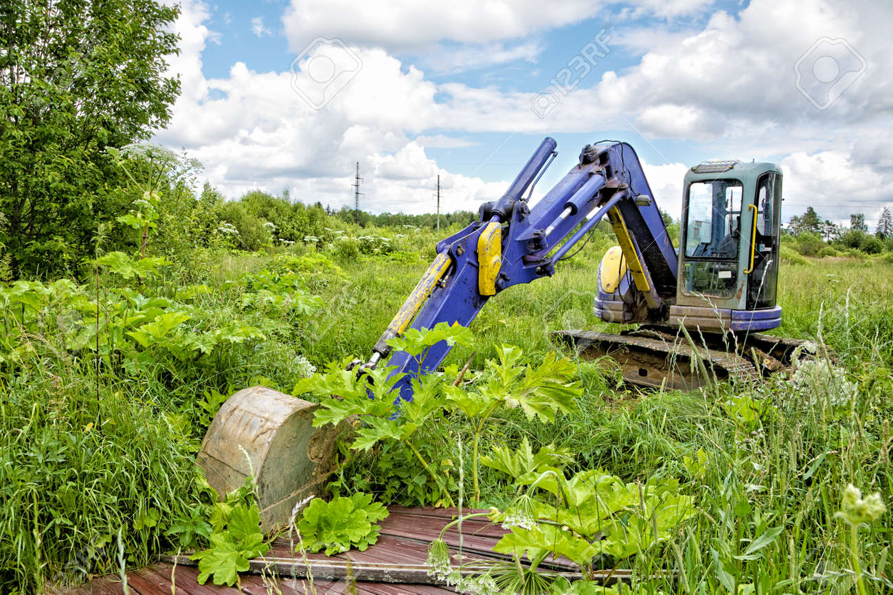 Caterpillar dredge in the field among a grass Stock Photo - 23909834