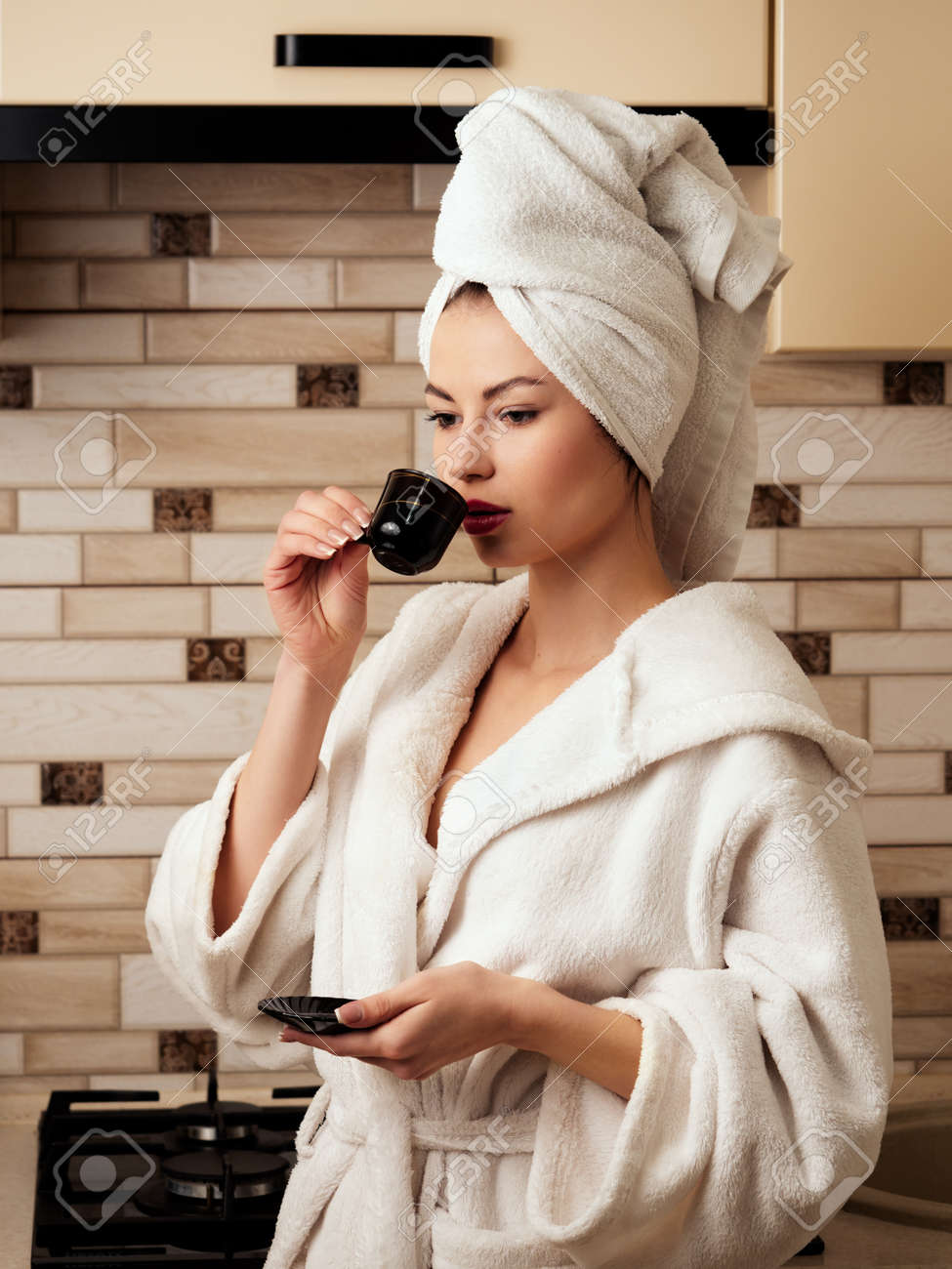 A young woman, a housewife in the kitchen, drinks coffee after a shower in a white bathrobe. - 167003138