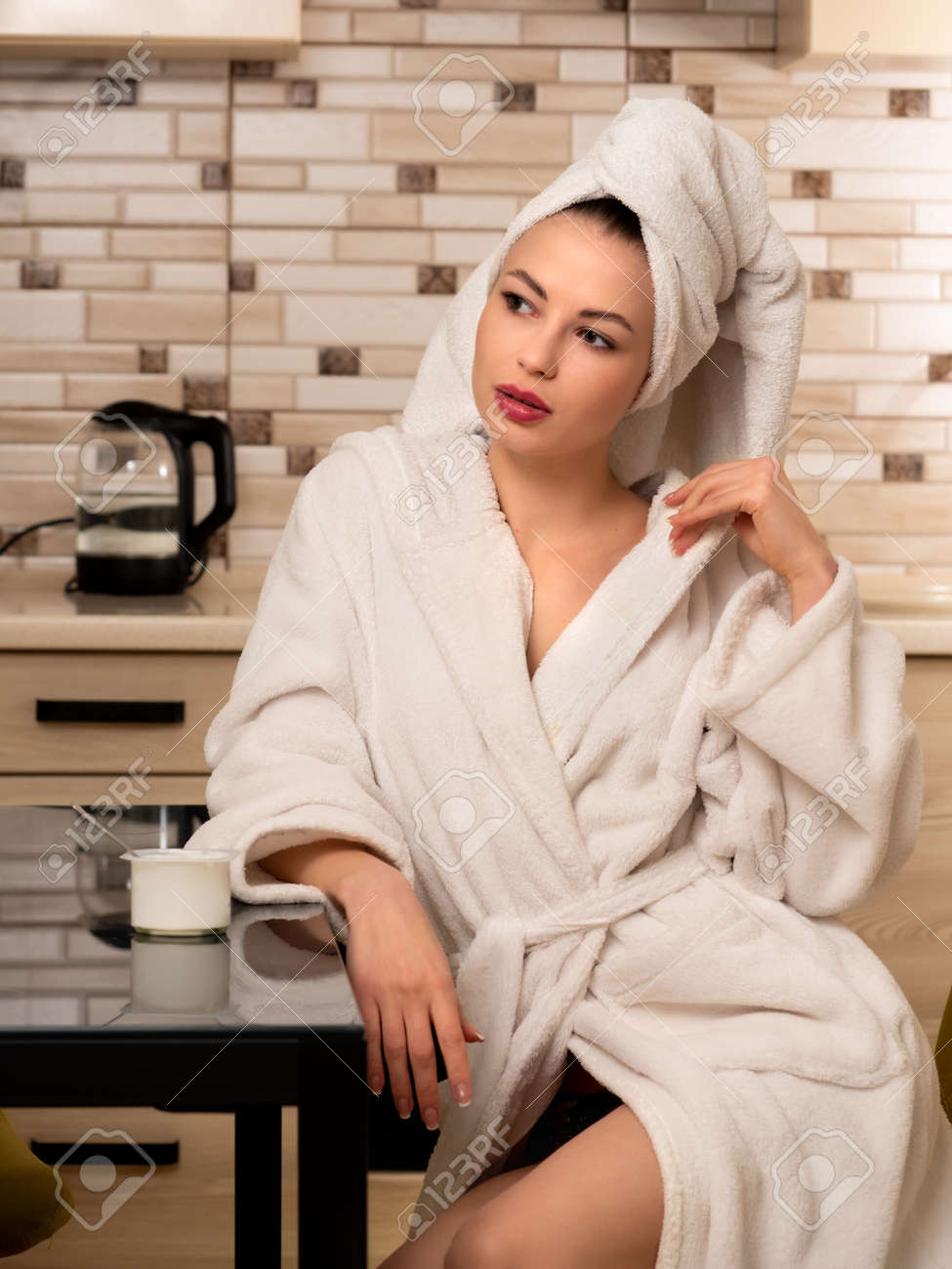 A young woman, a housewife in the kitchen sits at a table in a white bathrobe. - 167003139