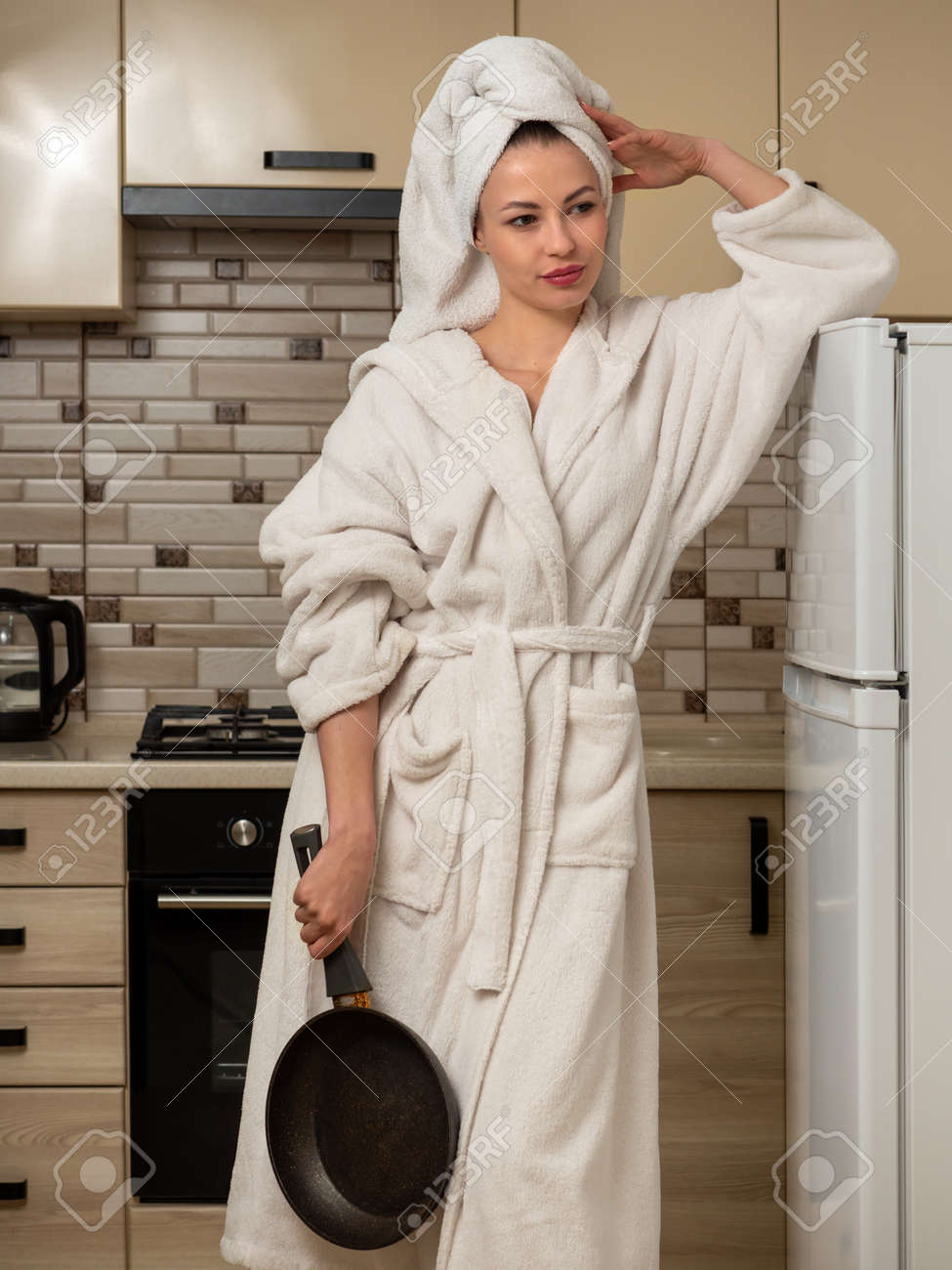 Young woman, housewife in the kitchen in a white, bathrobe with a frying pan. - 167003140