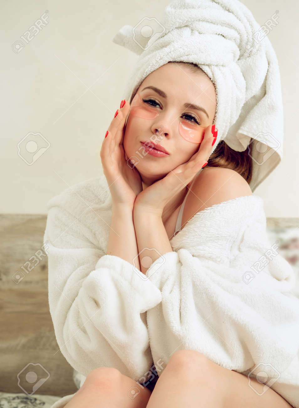 Young, beautiful woman cares for the skin of the face. Woman in robe after shower - 167782723
