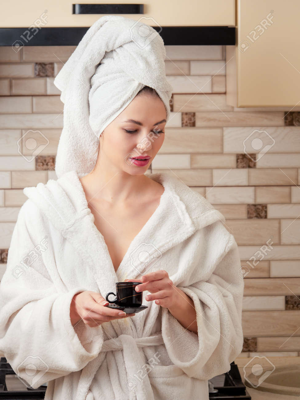 After a shower, a young, beautiful woman housewife in a white robe and a towel on her head is thinking with a cup of coffee in the kitchen. - 167782726