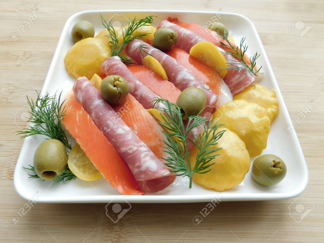 salami, olives and squash on a plate on a wooden table. traditional snacks - 165335634