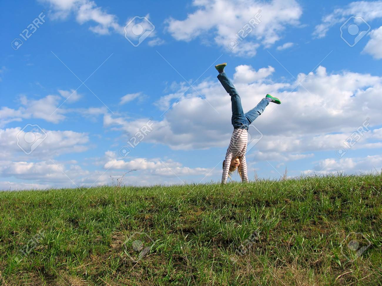 Somersault on grass on the sky&clouds background Stock Photo - 217605