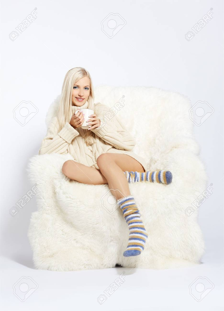 portrait of beautiful blonde sitting with cup on big white furry arm-chair Stock Photo - 7767901