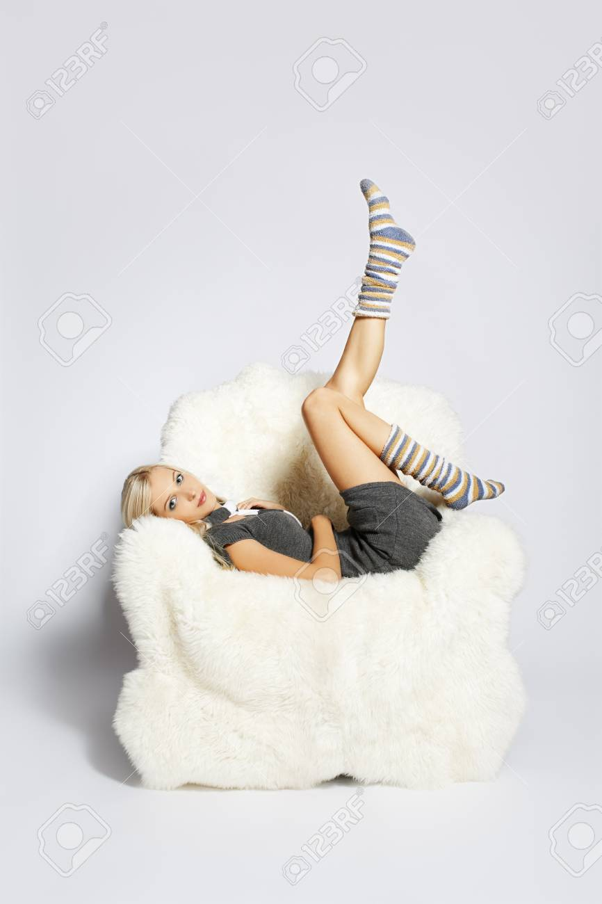 portrait of beautiful blonde sitting on big white furry arm-chair and putting on long striped socks Stock Photo - 7767902