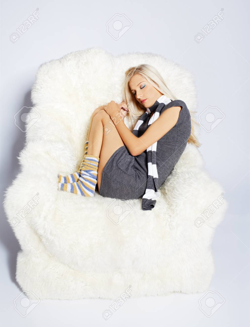 portrait of beautiful blonde sitting on big white furry arm-chair Stock Photo - 7767911