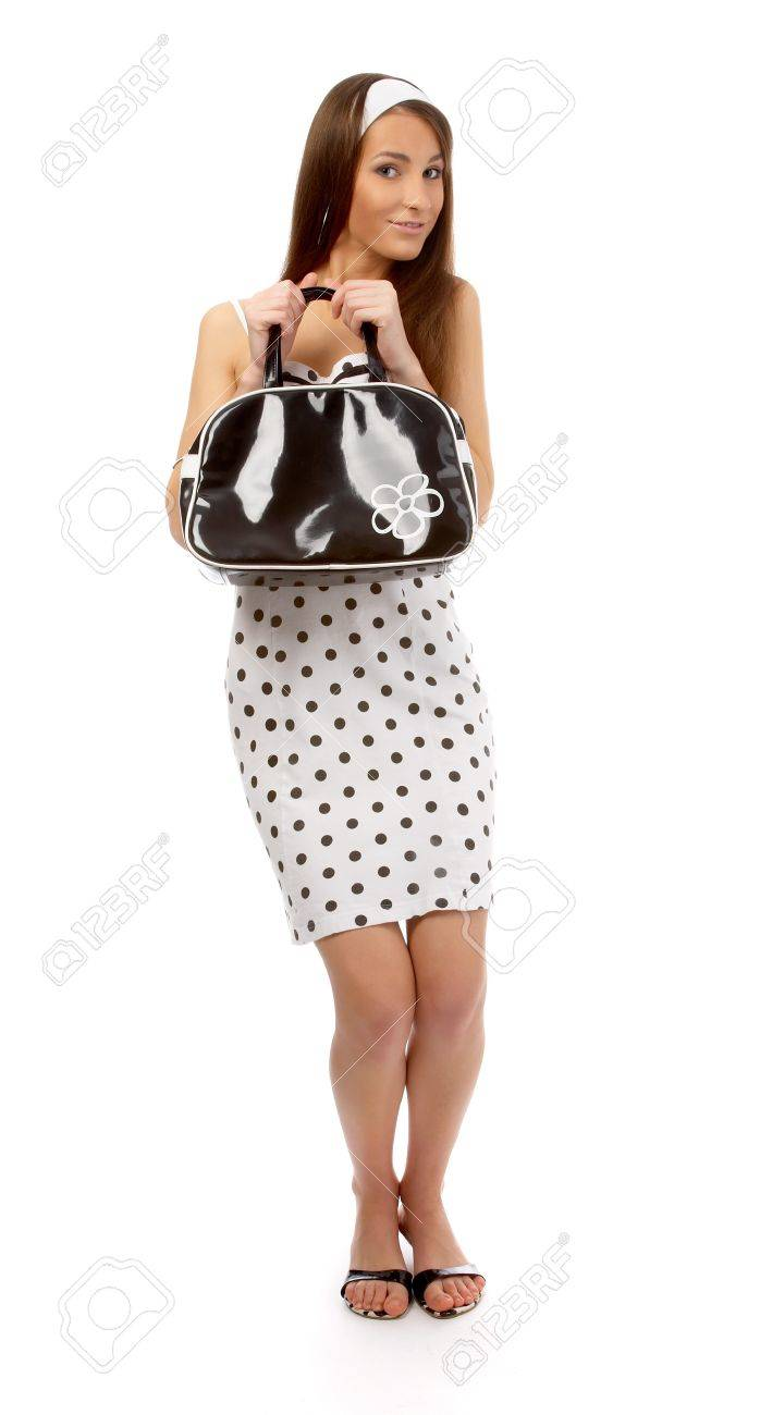 beautiful cheerful model poses in polka-dot dress with black bag on white Stock Photo - 8147172