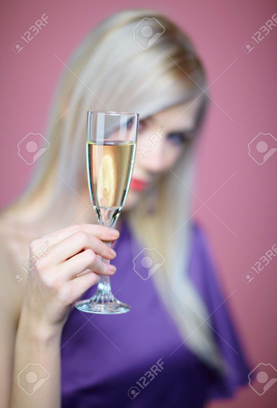 Low depth of field image -  beautiful blonde woman with glass of champagne on pink Stock Photo - 8216349