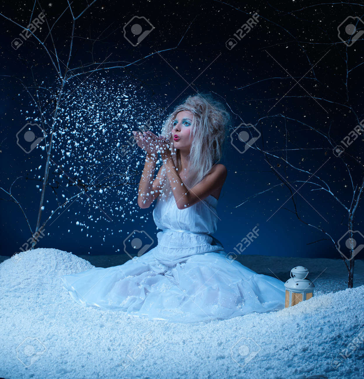 portrait of beautiful frozen fairy nymph girl sitting on snow and blowing snowflakes from her hands Stock Photo - 8305736