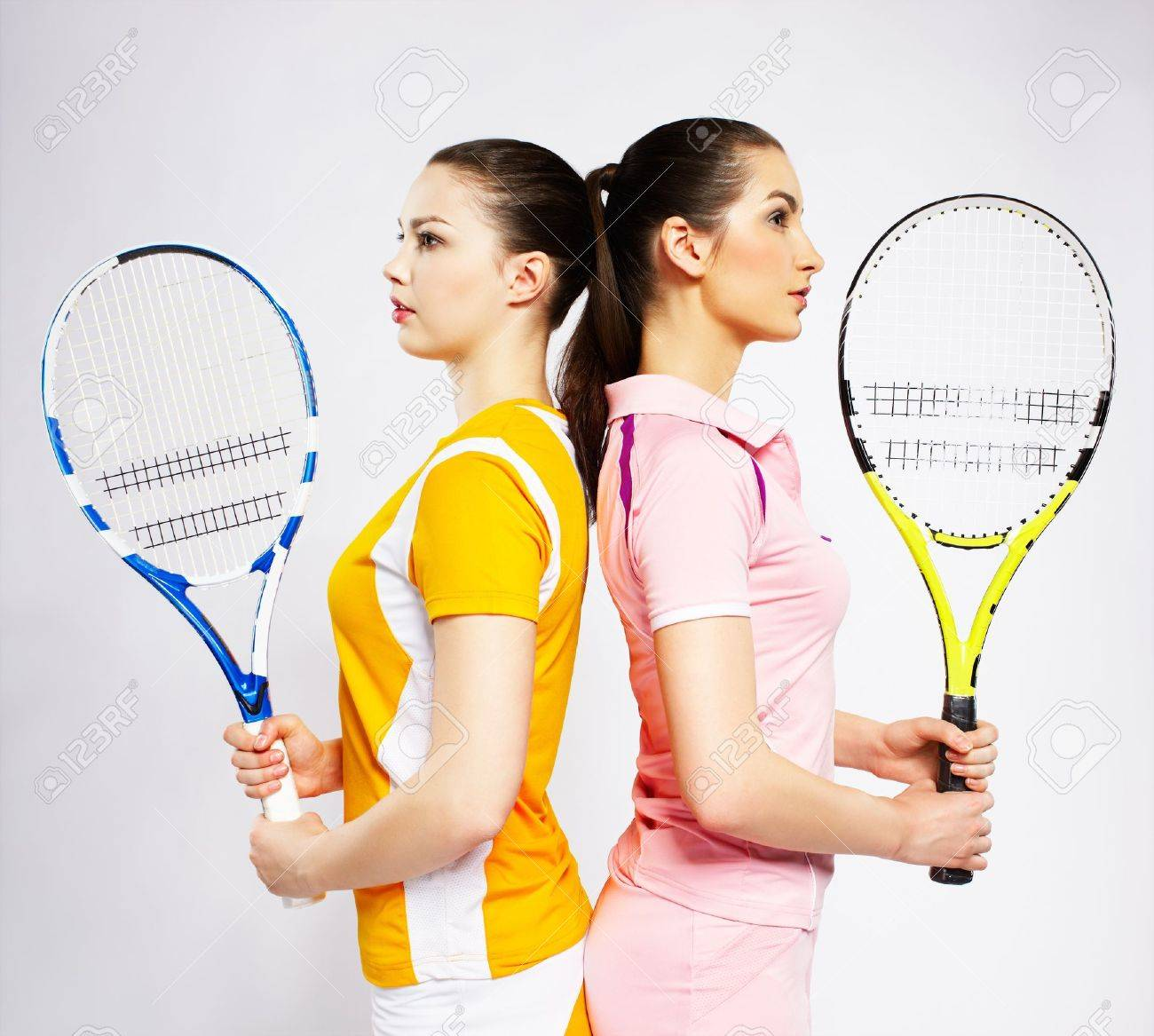 portrait of two sporty girls tennis players with rackets standing back to back Stock Photo - 8443247