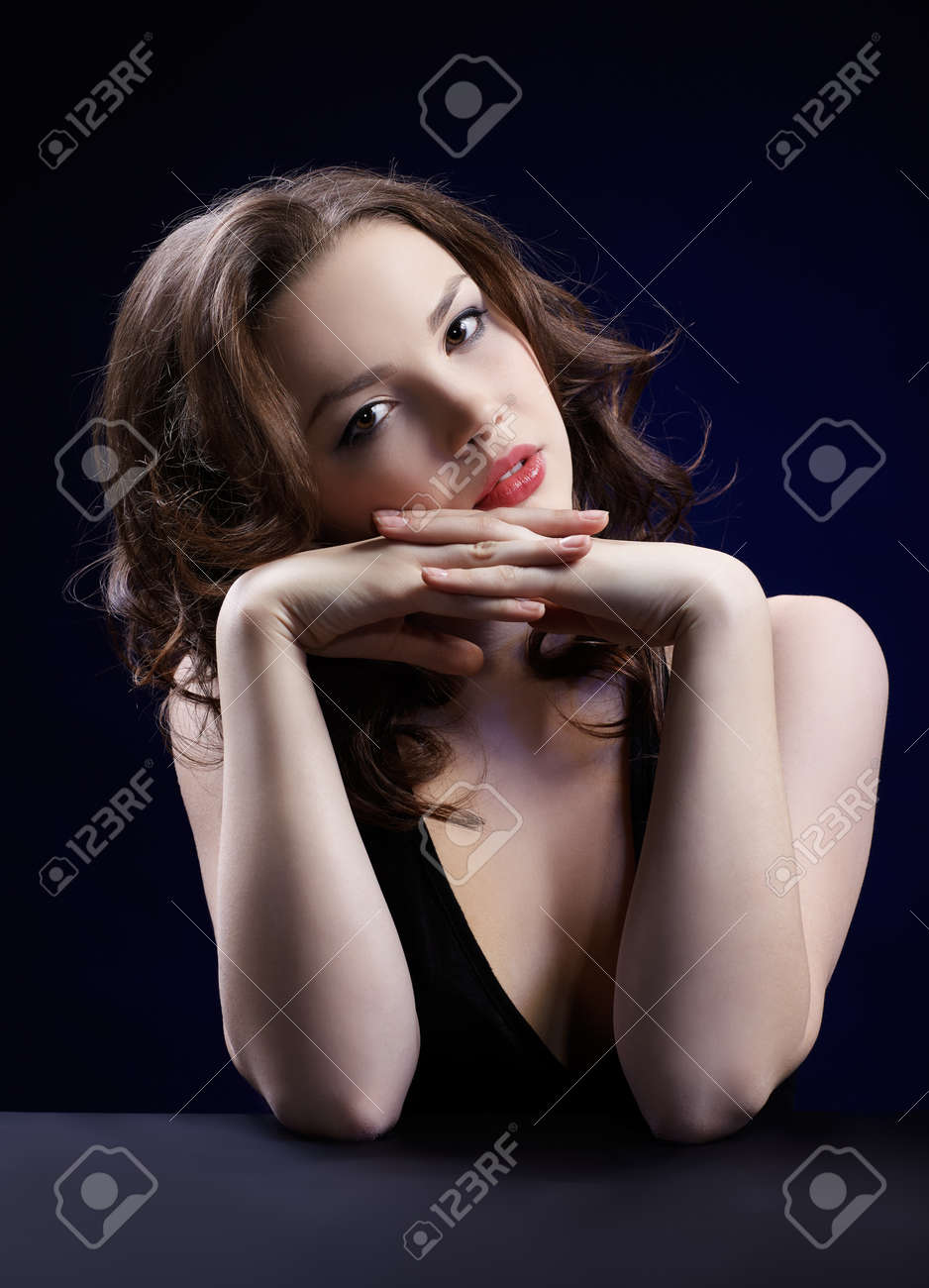 portrait of beautiful long-haired curly brunette girl on blue Stock Photo - 8658316