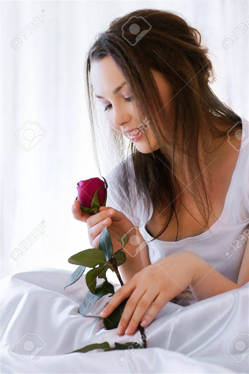 portrait of beautiful happy girl relaxing in bedroom on linen with red rose Stock Photo - 8806212