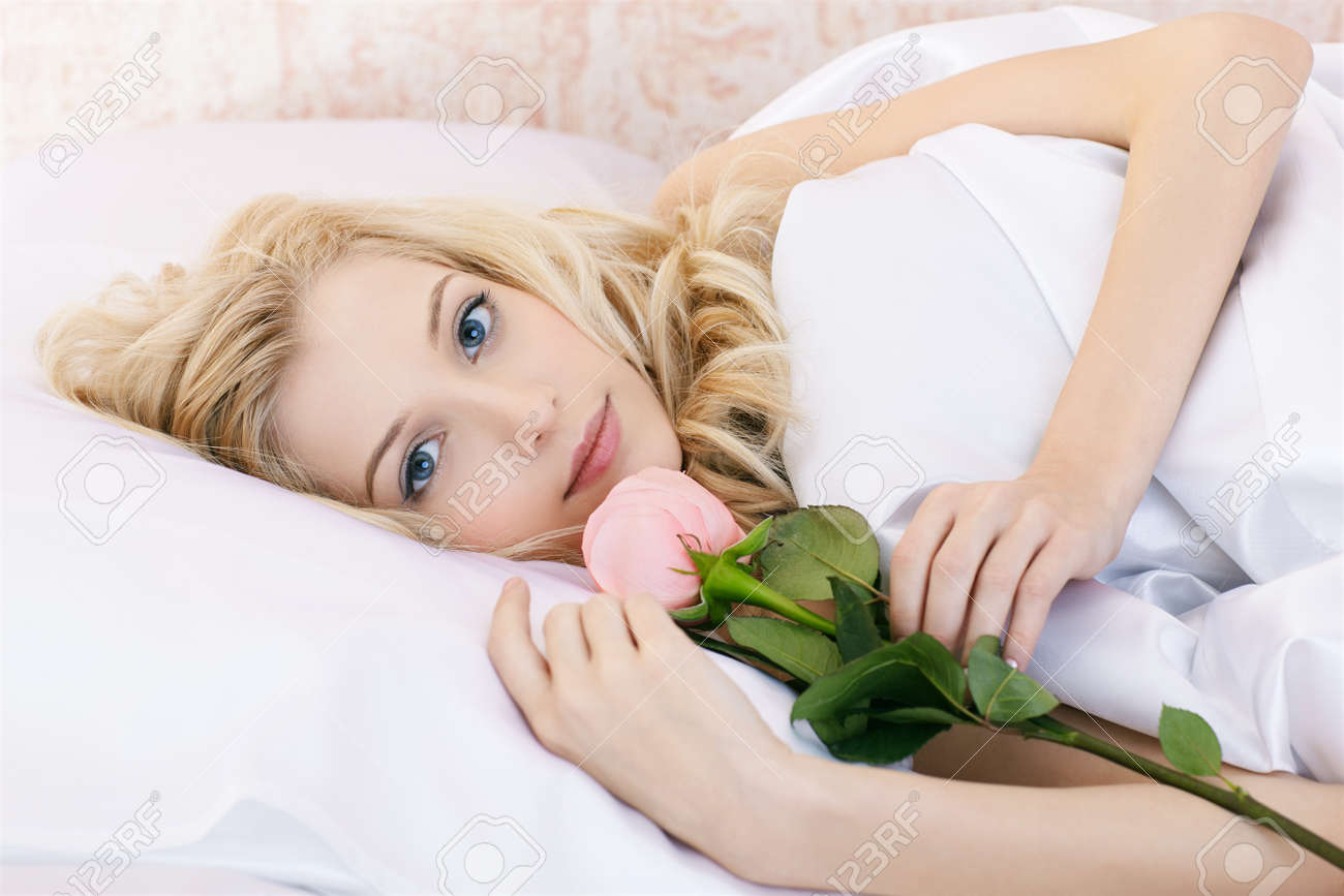 portrait of beautiful happy blonde girl relaxing in bedroom on linen with pink rose Stock Photo - 8806161