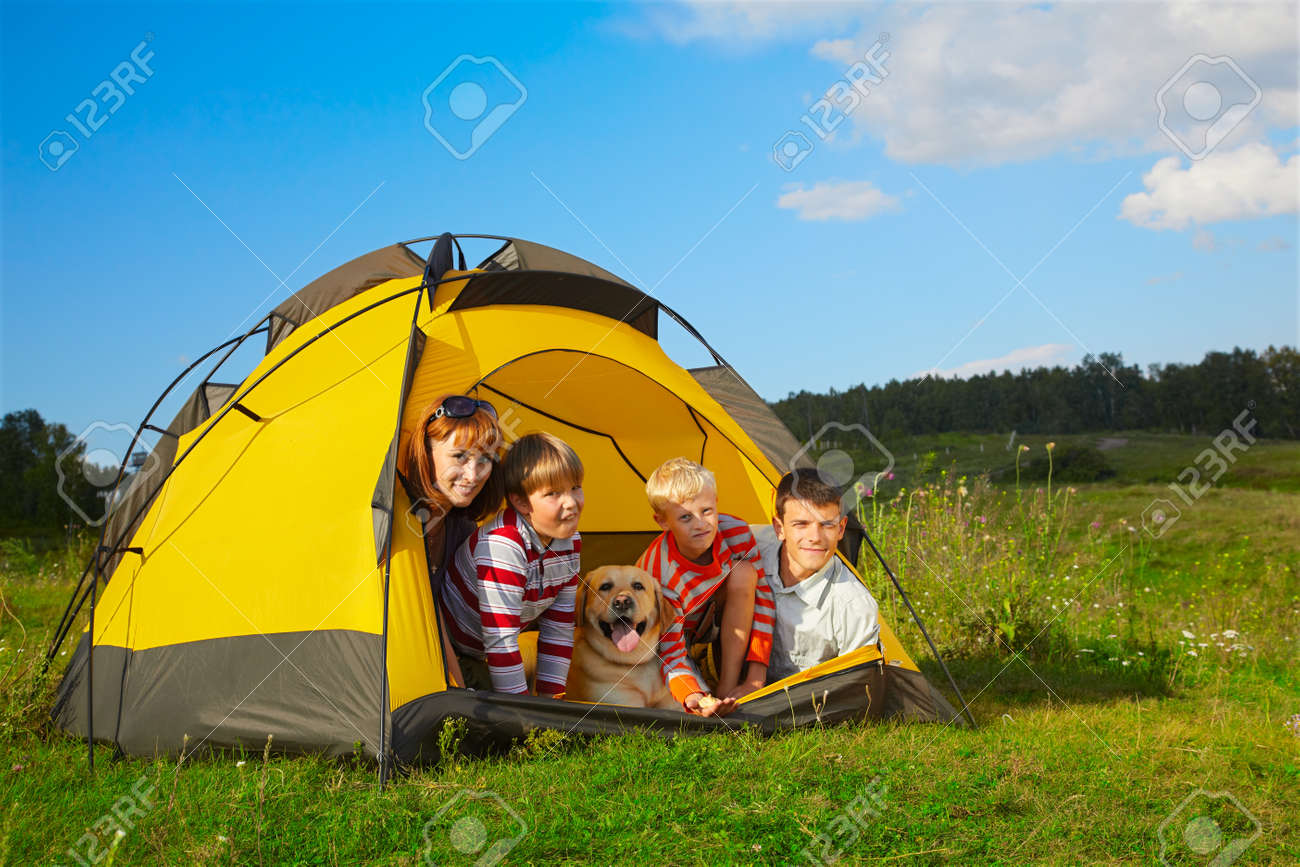 family outdoor portrait of smiling mother, two boys, young man and labrador looking happy outside of tent Stock Photo - 8806325