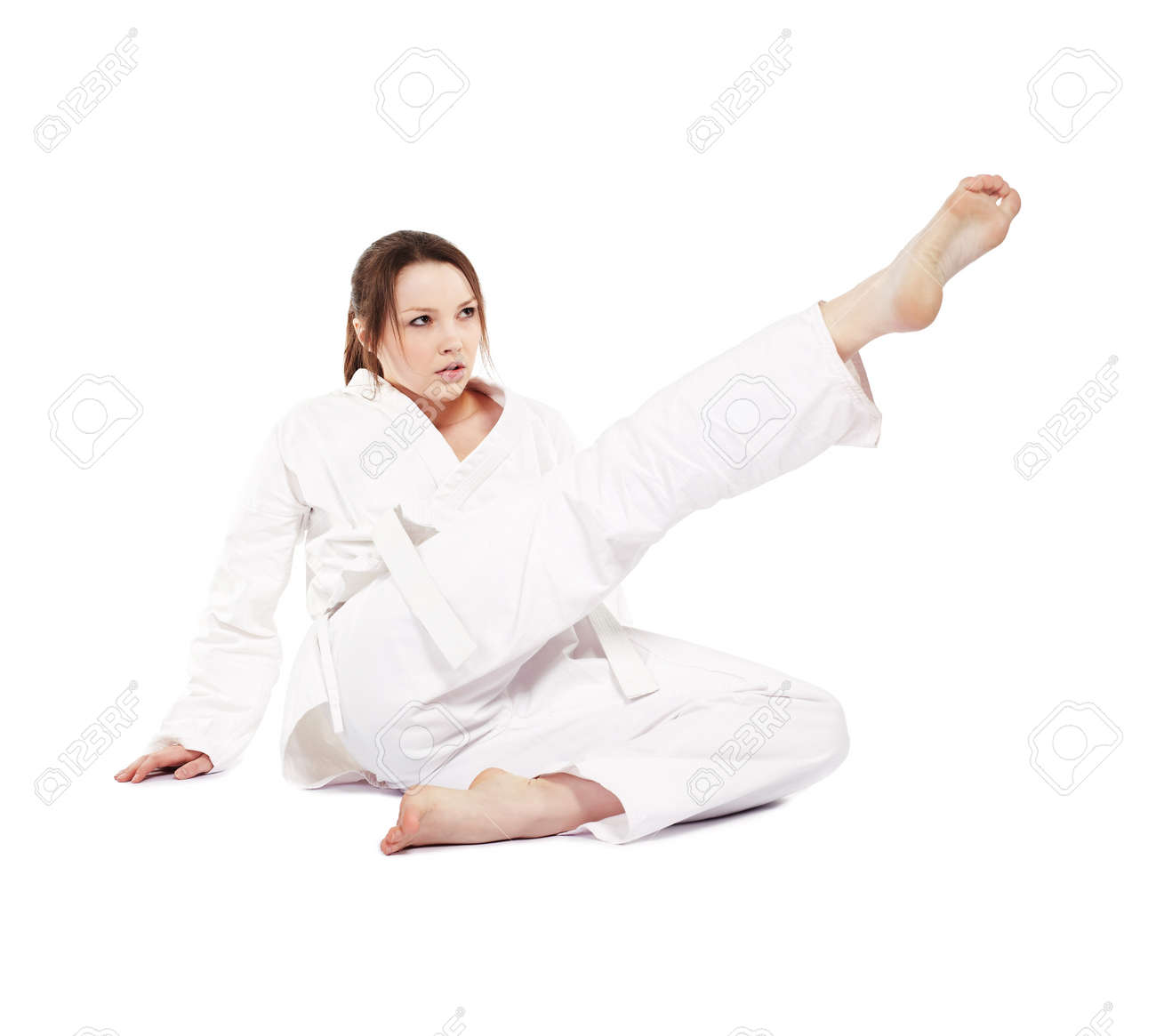 full-length isolated portrait of beautiful martial arts girl in kimono excercising karate kata kick from the land Stock Photo - 9340235