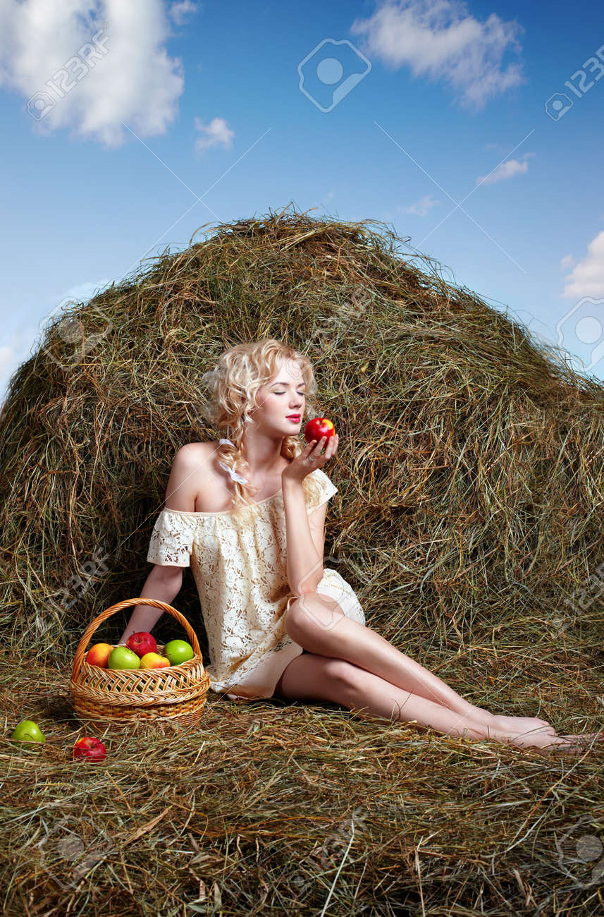 portrait of beautiful blonde country girl posing on yellow hay with basket of apples Stock Photo - 9599740