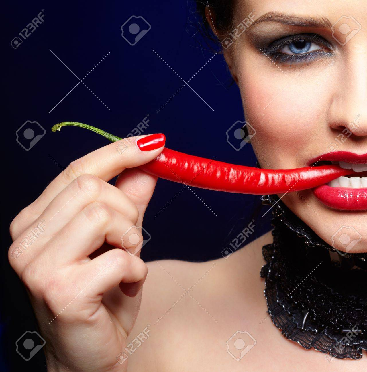 portrait of beautiful brunette girl in black lacy collar biting spicy hot red cayenne Stock Photo - 9970884