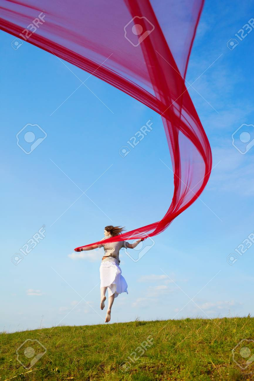 outdoor portrait of beautiful hippie girl jumping with big piece of red light cloth under the blue sky Stock Photo - 9971053