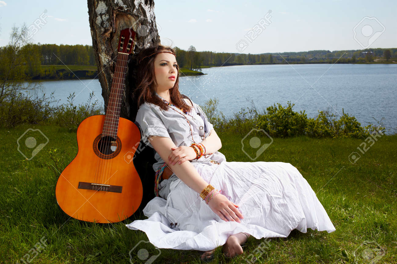 outdoor portrait of beautiful hippie girl sitting on green grass near birch with guitar. lake and forest on background Stock Photo - 9969425