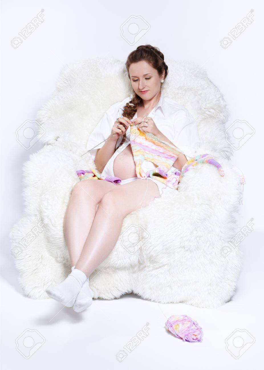 portrait of young beautiful pregnant woman in white furry arm-chair knitting baby's looses Stock Photo - 10280472