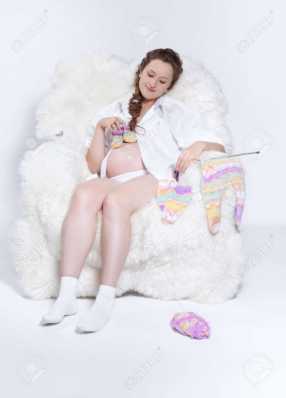 portrait of young beautiful pregnant woman in white furry arm-chair knitting baby's looses Stock Photo - 10280485