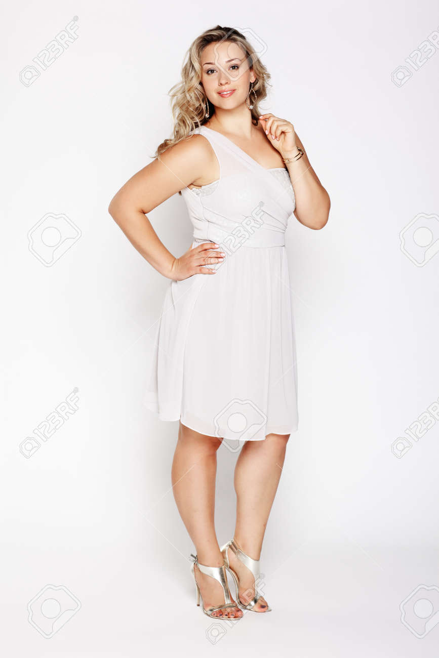 full-length portrait of beautiful plus size curly young blond woman posing on gray in white dress and court shoes Stock Photo - 10479144
