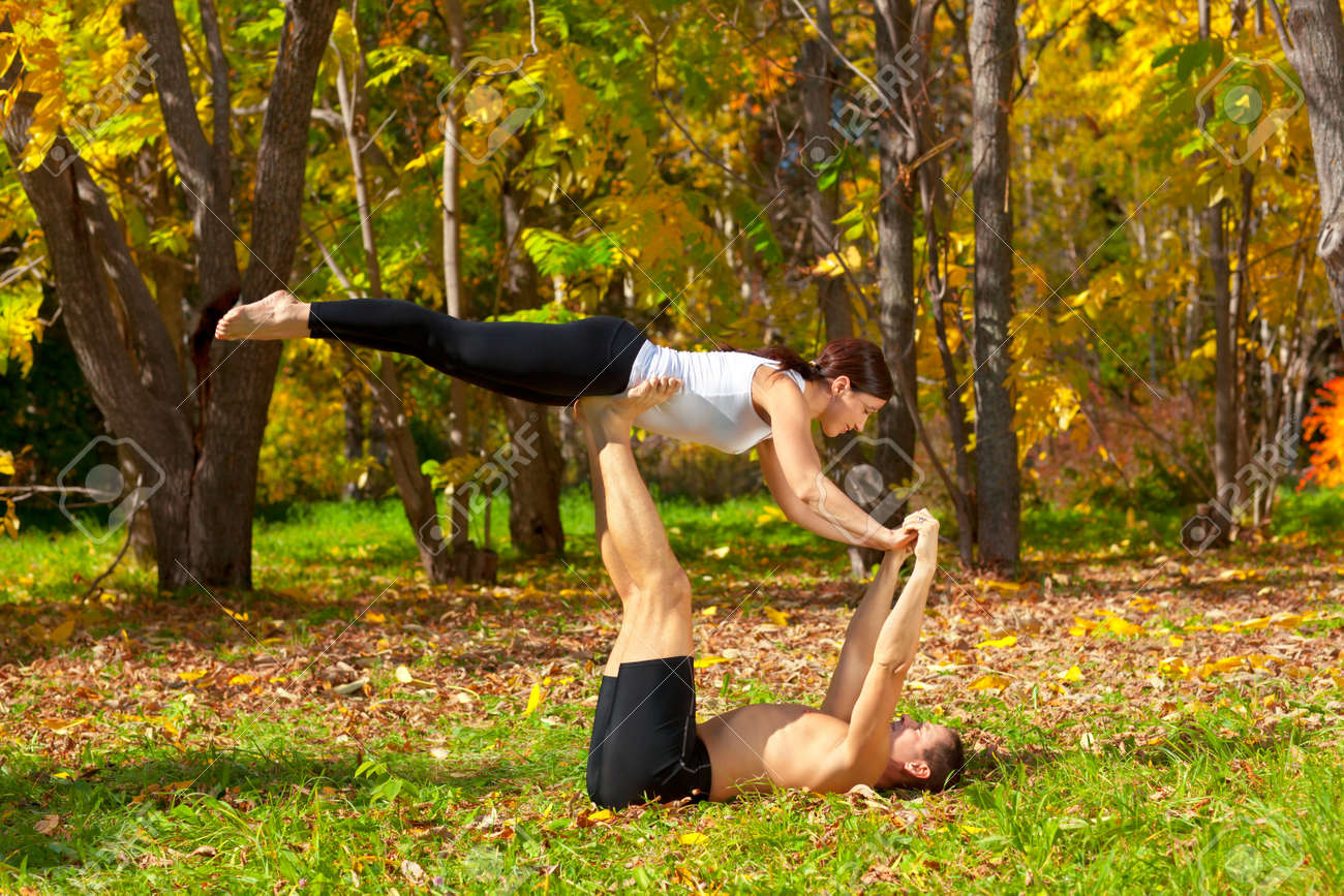 An attractive  man and woman practice tantra yoga in forest Stock Photo - 11727280
