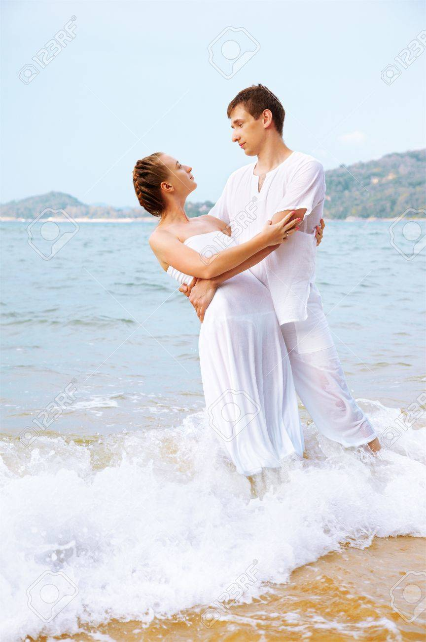 outdoor portrait of young romantic couple in white cotton clothes embracing each other on beach of Phuket island, Thailand Stock Photo - 11727232