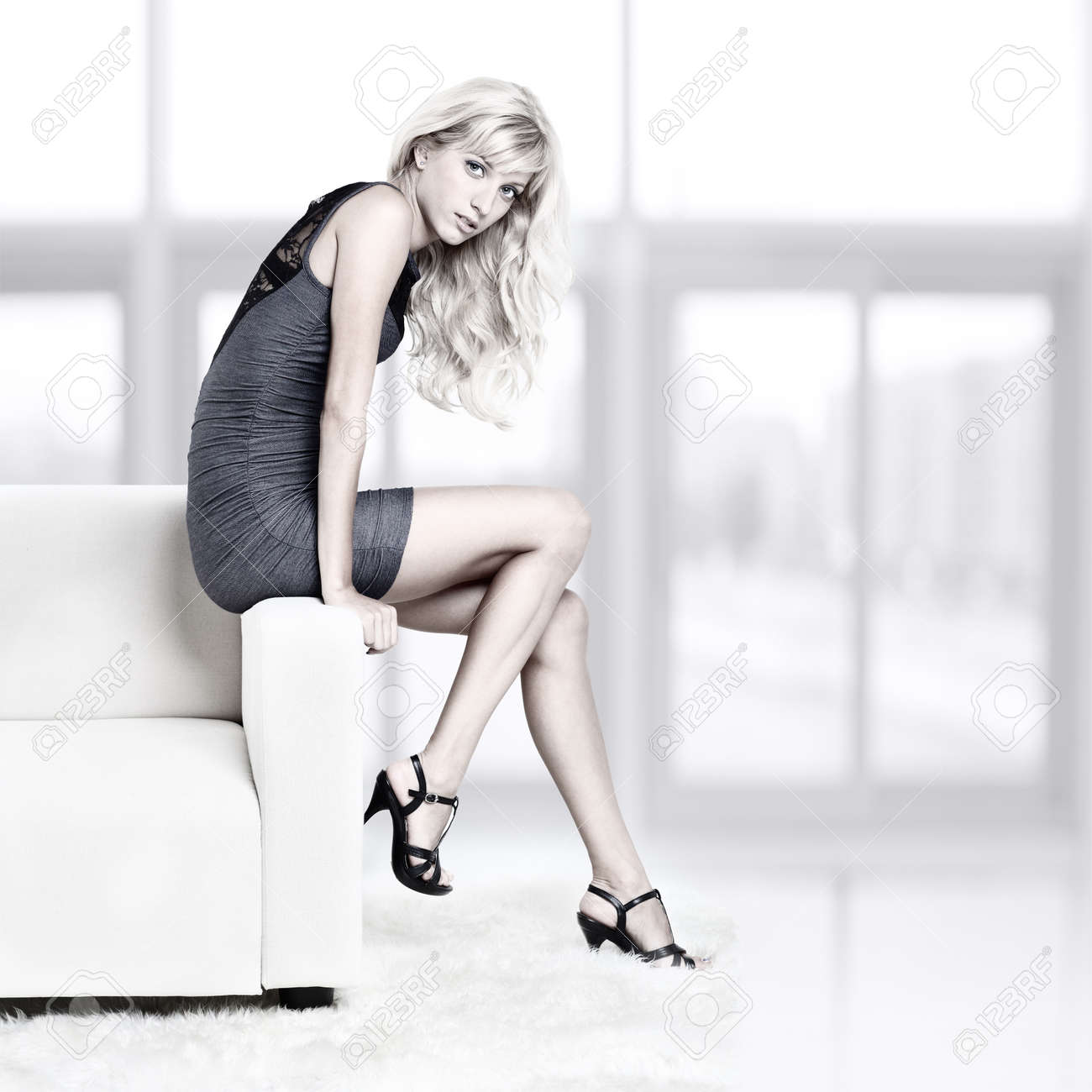 full-length portrait of beautiful young blond woman on couch with white furs on floor Stock Photo - 12106036