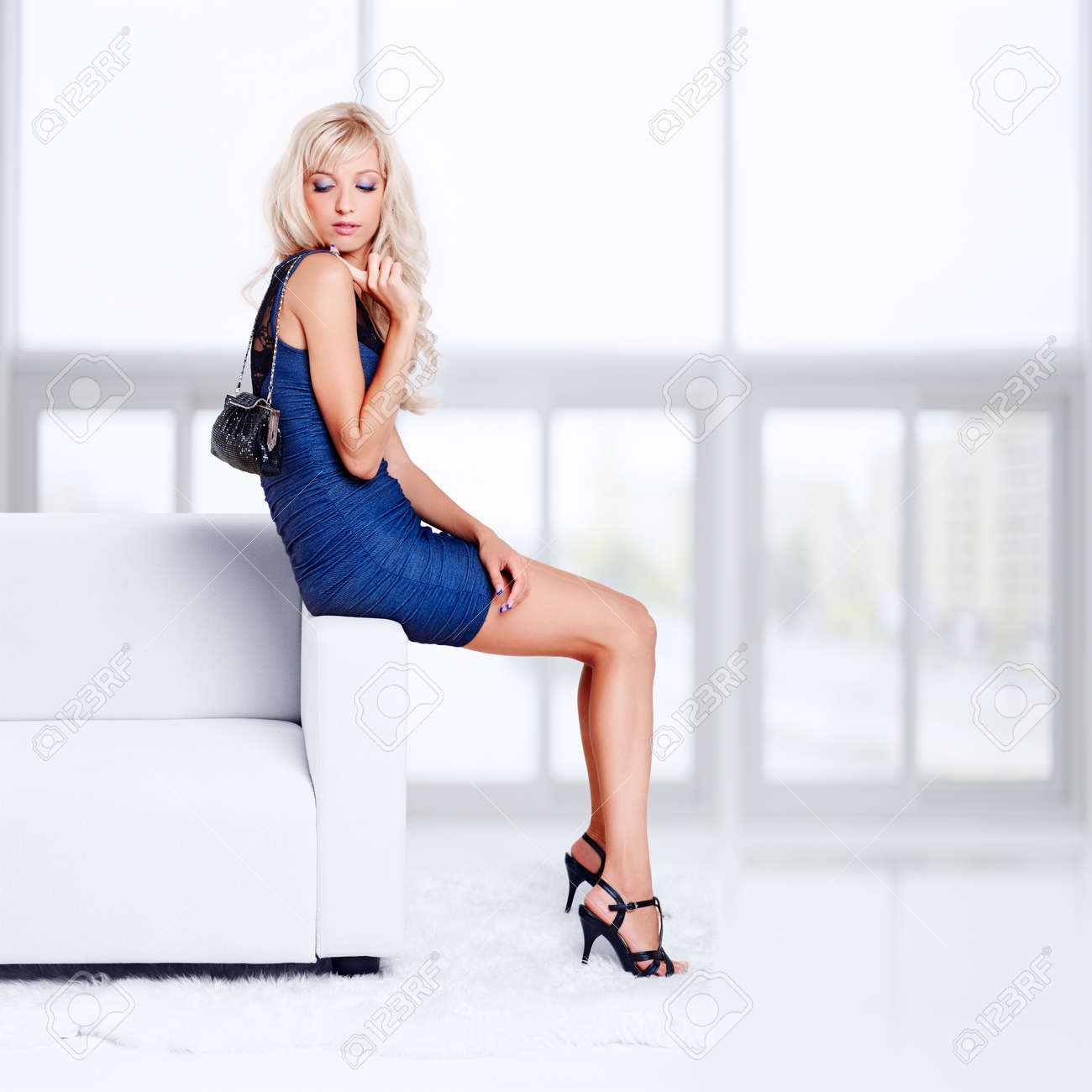 full-length portrait of beautiful young blond woman with handbag sitting on couch with white furs on floor Stock Photo - 12106078