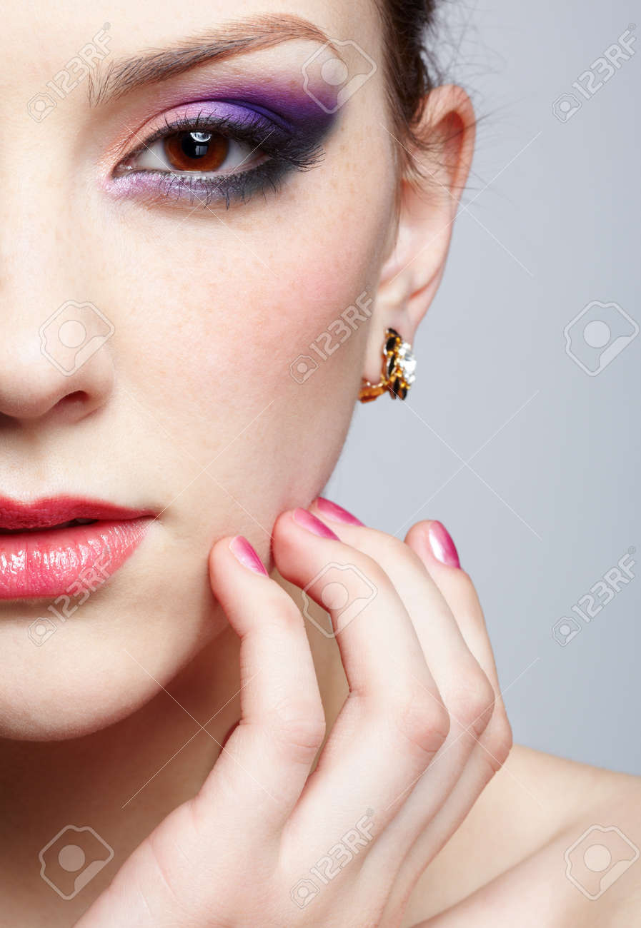 close-up half-face portrait of young beautiful woman with violet eye shadow touching her face with manicured fingers - 12333652