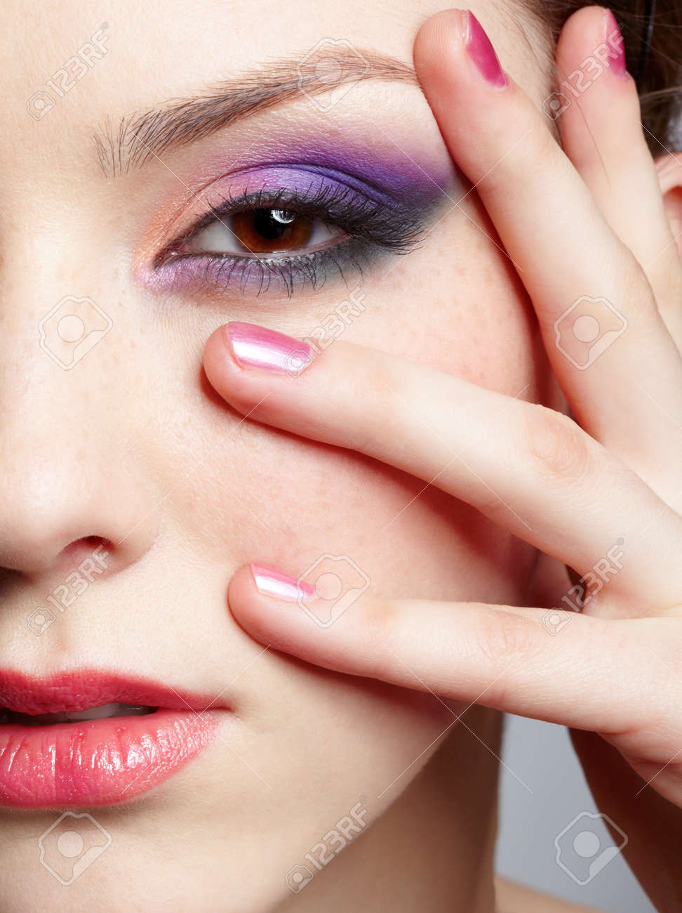 close-up half-face portrait of young beautiful woman with violet eye shadow touching her face with manicured hand Stock Photo - 12341941