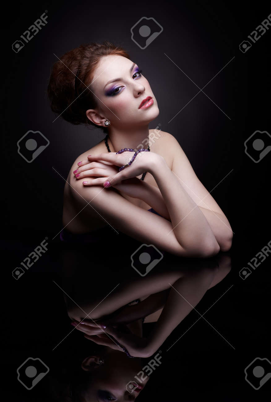 portrait of beautiful young woman sitting at dark mirror table Stock Photo - 12341988