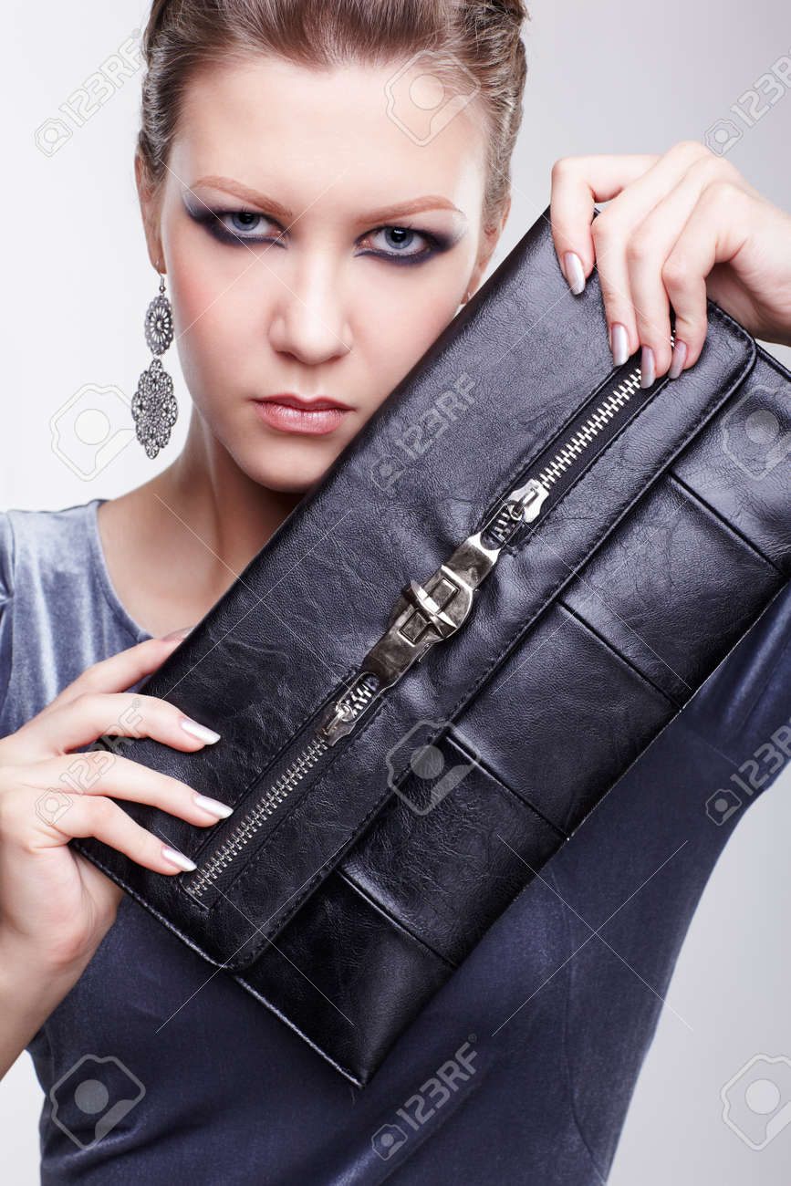 portrait of beautiful young brunette woman in stylish dress holding clutch with both hands Stock Photo - 13208674