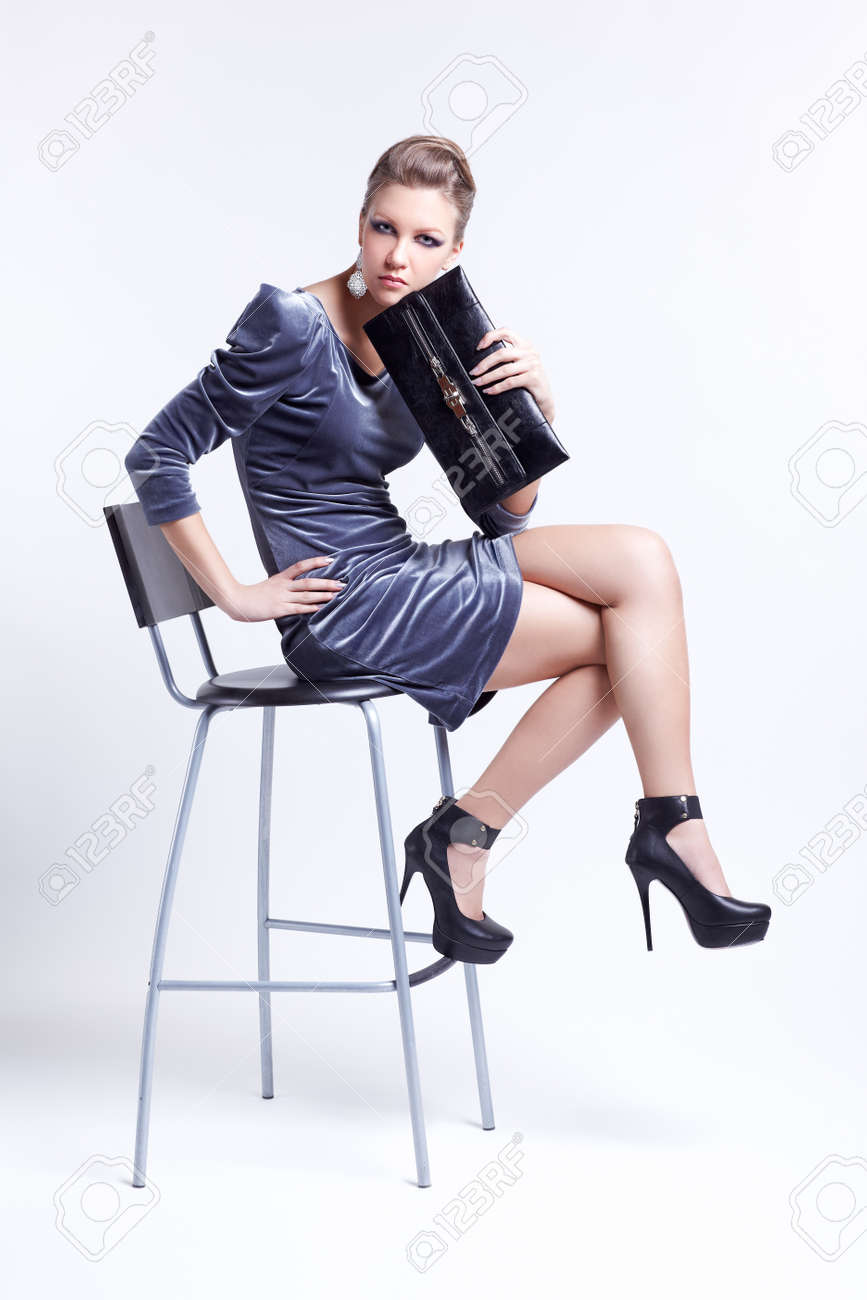 full-length portrait of beautiful young brunette business woman in fancy dress sitting on bar stool with clutch in hand Stock Photo - 13208583