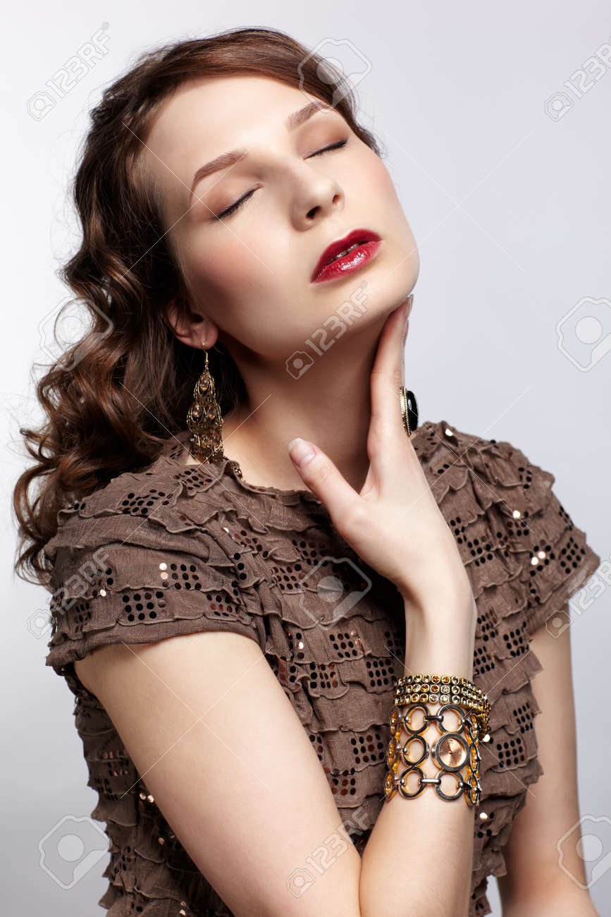 portrait of beautiful young brunette woman in various jewelry touching her neck and closing eyes Stock Photo - 13287054