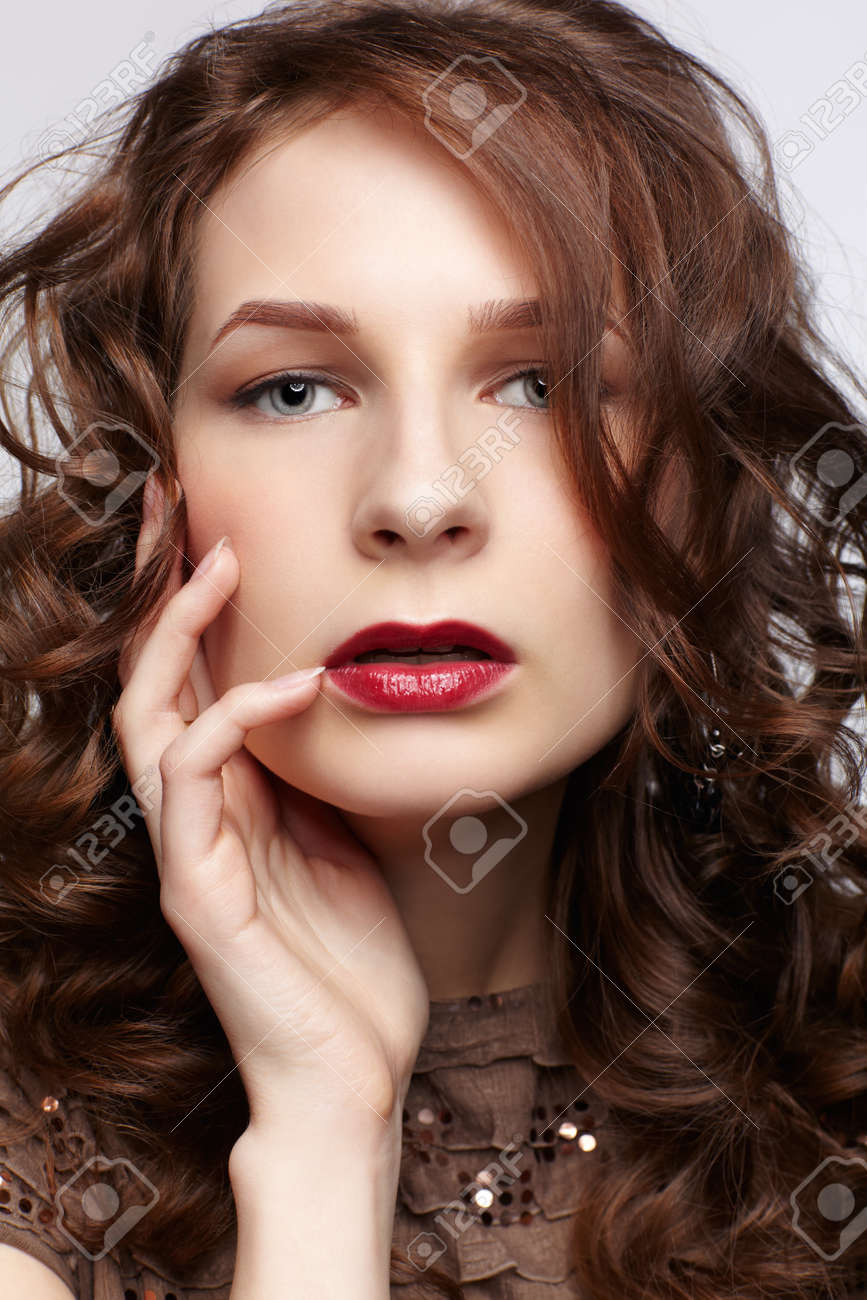 portrait of beautiful young brunette woman touching her face with manicured fingers on gray Stock Photo - 13287046